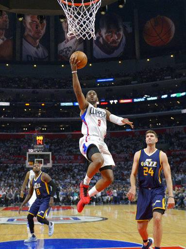 FILE - In this April 15, 2017, file photo, Los Angeles Clippers guard Chris Paul, center, shoots as Utah Jazz guard Shelvin Mack, left, and center Jeff Withey defend during the second half in Game 1 of an NBA basketball first-round playoff series in Los Angeles. Paul's return to his old Clippers home is part of a Martin Luther King Jr. day tripleheader that includes another NBA Finals rematch. (AP Photo/Mark J. Terrill, File)