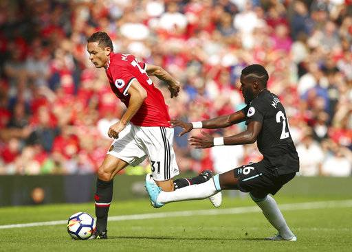 Manchester United's Nemanja Matic, left, gets past West Ham United's Arthur Masuaku during the English Premier League soccer match between Manchester United and West Ham United at Old Trafford in Manchester, England, Sunday, Aug. 13, 2017. (AP Photo/Dave Thompson)