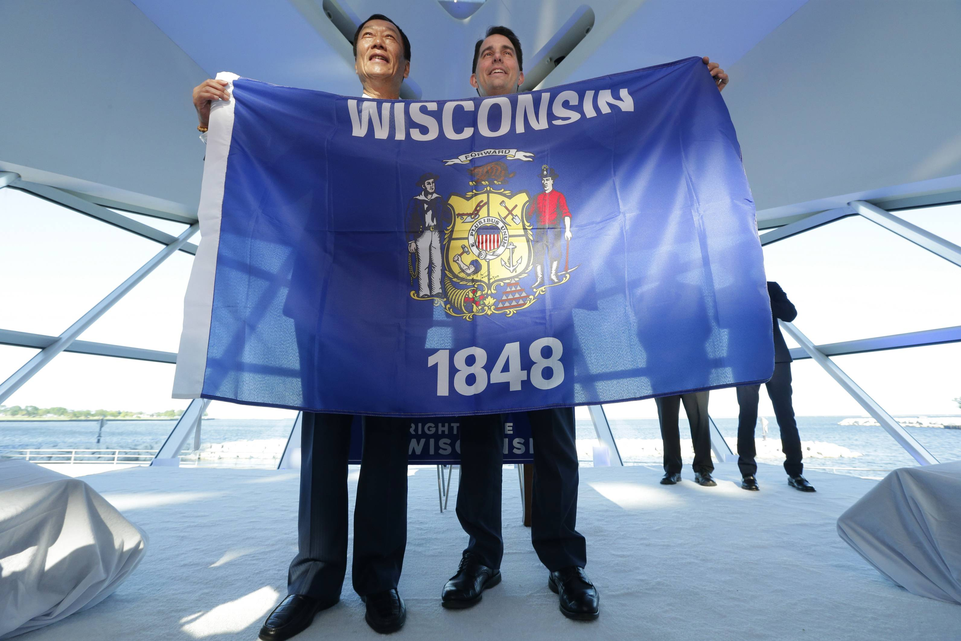 Foxconn Chairman Terry Gou, left, and Gov. Scott Walker hold the Wisconsin flag to celebrate their $10 billion investment to build a display panel plant in Wisconsin. The company's interest in building has triggered a debate about government efforts to lure companies via tax breaks, betting the public will benefit in the long run from spikes in economic activity.