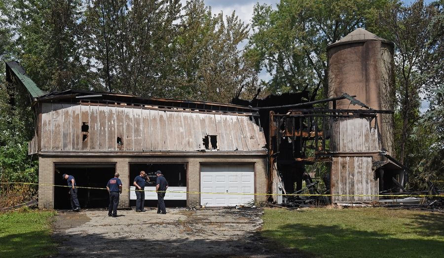 Geneva fire officials look over the damage after a large storage barn was severely damaged by a fire Monday on Kaneville Road.