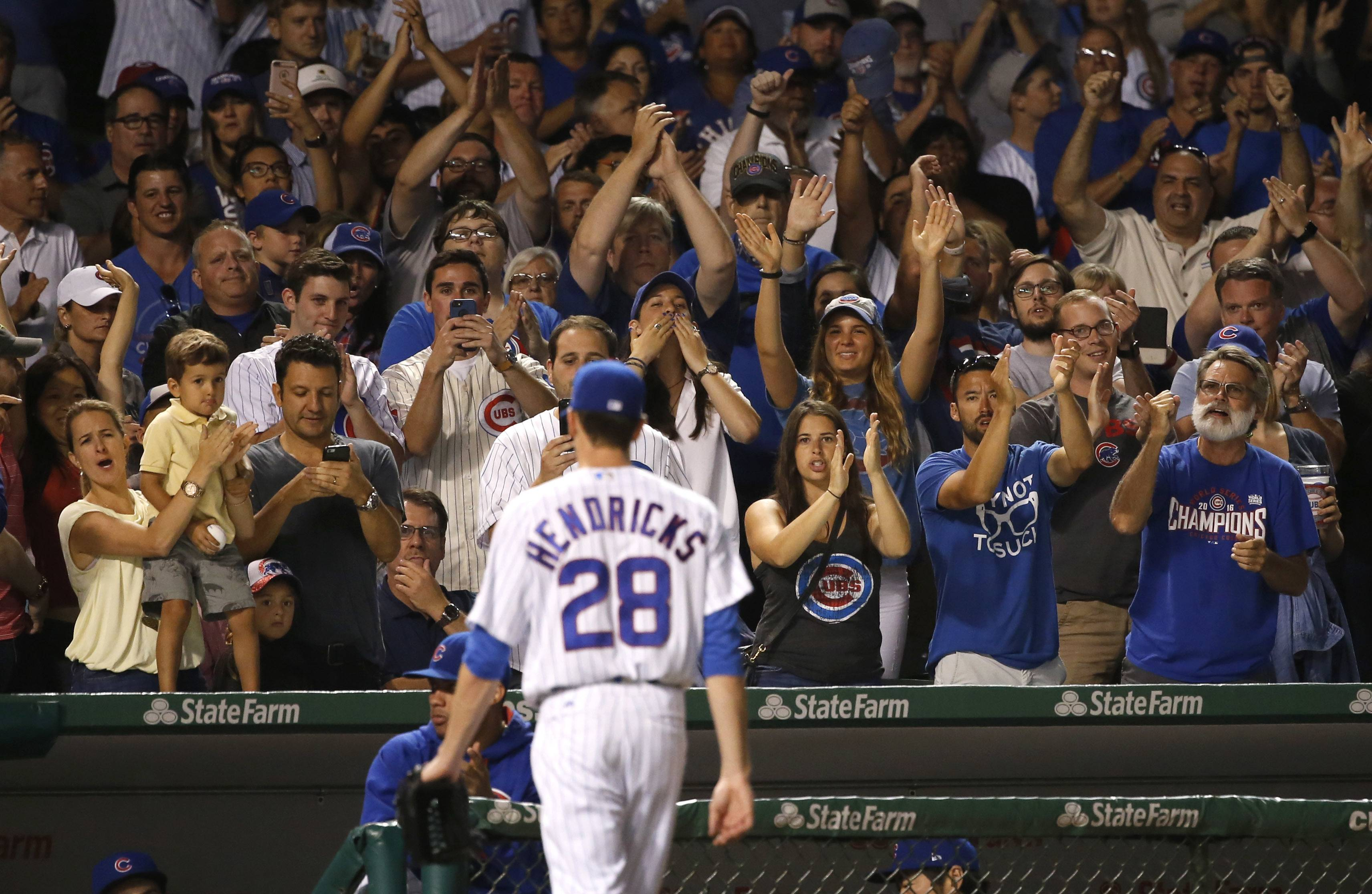 Fans applaud Chicago Cubs starting pitcher Kyle Hendricks as he leaves the baseball game during the seventh inning against the Cincinnati Reds, Tuesday, Aug. 15, 2017, in Chicago. (AP Photo/Charles Rex Arbogast)