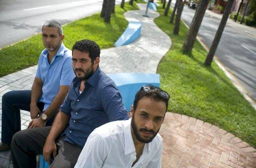 In this July 26, 2017 photo, Cuban architects Yasser Jimenez, left, Oriesky Bencomo, center, and Jose Luis Valdes, right, pose at the site of one of their urban designs in Pinar del Rio, Cuba. The three architects thought they'd work largely for private citizens renovating their homes as bed-and-breakfasts. However in 2014, the team learned that the provincial government was asking state-run engineering firms to bid on renovating the median strip of Calle Marti. They bid for the design of the project and won, convincing officials it could do the work quickly and more efficiently. (AP Photo/Ramon Espinosa)