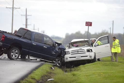 FILE - In this April 14, 2017, file photo, law enforcement investigate a quadruple fatal car accident on Riverside Road in St. Joseph, Mo. New data show U.S. motor vehicle deaths and injuries were down slightly in the first six months of 2017, although they were still significantly higher than they were two years ago. The preliminary figures were compiled by the National Safety Council, which gets its data from state governments. (Jessica A. Stewart/The St. Joseph News-Press via AP)