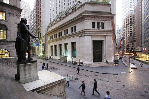 FILE - In this Oct. 8, 2014, file photo, people walk to work on Wall Street beneath a statue of George Washington, in New York. Stock markets around the world remained buoyed Tuesday, Aug. 15, 2017, by a seeming further easing in tensions between the United States and North Korea, which has helped investors rediscover their appetite for riskier assets following last week's aversion. (AP Photo/Mark Lennihan, File)