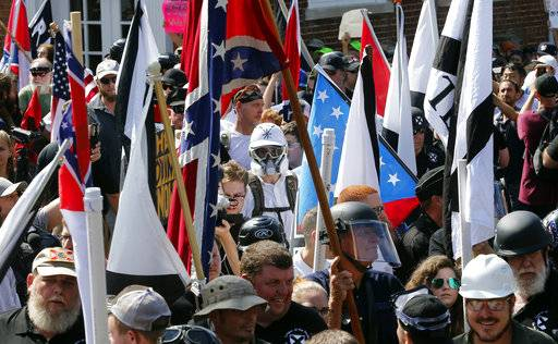 "FILE- In this Saturday, Aug. 12, 2017, photo white nationalist demonstrators walk into the entrance of Lee Park surrounded by counter demonstrators in Charlottesville, Va. The Detroit Lions said Tuesday, Aug. 15, that they ""detest and disavow� any use of their logo associated with the event Saturday in Charlottesville. A photo taken at the demonstration showed someone with a logo similar to the one the Lions use, although it was blue and red and had stars on it. (AP Photo/Steve Helber, File)"