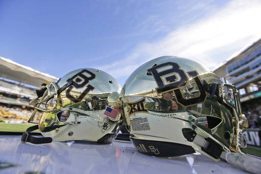 FILE - In this Dec. 5, 2015, file photo, Baylor helmets on shown the field after an NCAA college football game in Waco, Texas. The first woman to sue Baylor University over allegations the nation's largest Baptist school ignored or mishandled rape allegations has settled her case, her attorney said Tuesday, Aug. 15, 2017. (AP Photo/LM Otero, File)