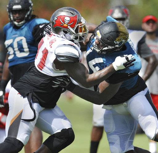Tampa Bay Buccaneers defensive end Robert Ayers Jr., left, goes against Jacksonville Jaguars offensive lineman Cam Robinson during a joint NFL football practice Monday, Aug. 14, 2017, in Jacksonville, Fla. (Will Dickey/Florida Times-Union)