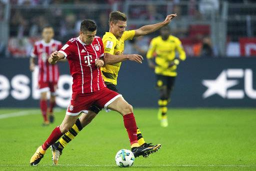 FILE - In this Aug. 5, 2017 photo Dortmund's Lukasz Piszczek, right, and Bayern's Robert Lewandowski vie for the ball during the Supercup soccer final between FC Bayern Munich and Borussia Dortmund in the Signal-Iduna-Park in Dortmund, Germany. Bayern Munich will face Bayer Leverkusen in an opening match for the new season on Friday, Aug. 18, 2017. (Marius Becker/dpa via AP,file)