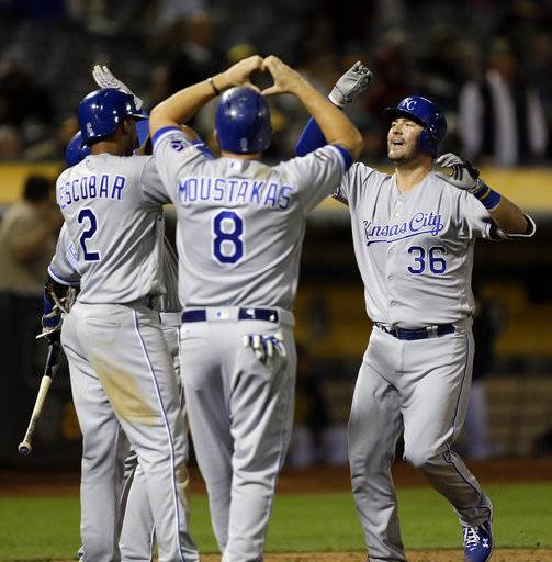 Kansas City Royals' Cam Gallagher, right, celebrates with Mike Moustakas (8) and Alcides Escobar (2) after hitting a grand slam off Oakland Athletics' Jharel Cotton in the sixth inning of a baseball game, Monday, Aug. 14, 2017, in Oakland, Calif. (AP Photo/Ben Margot)