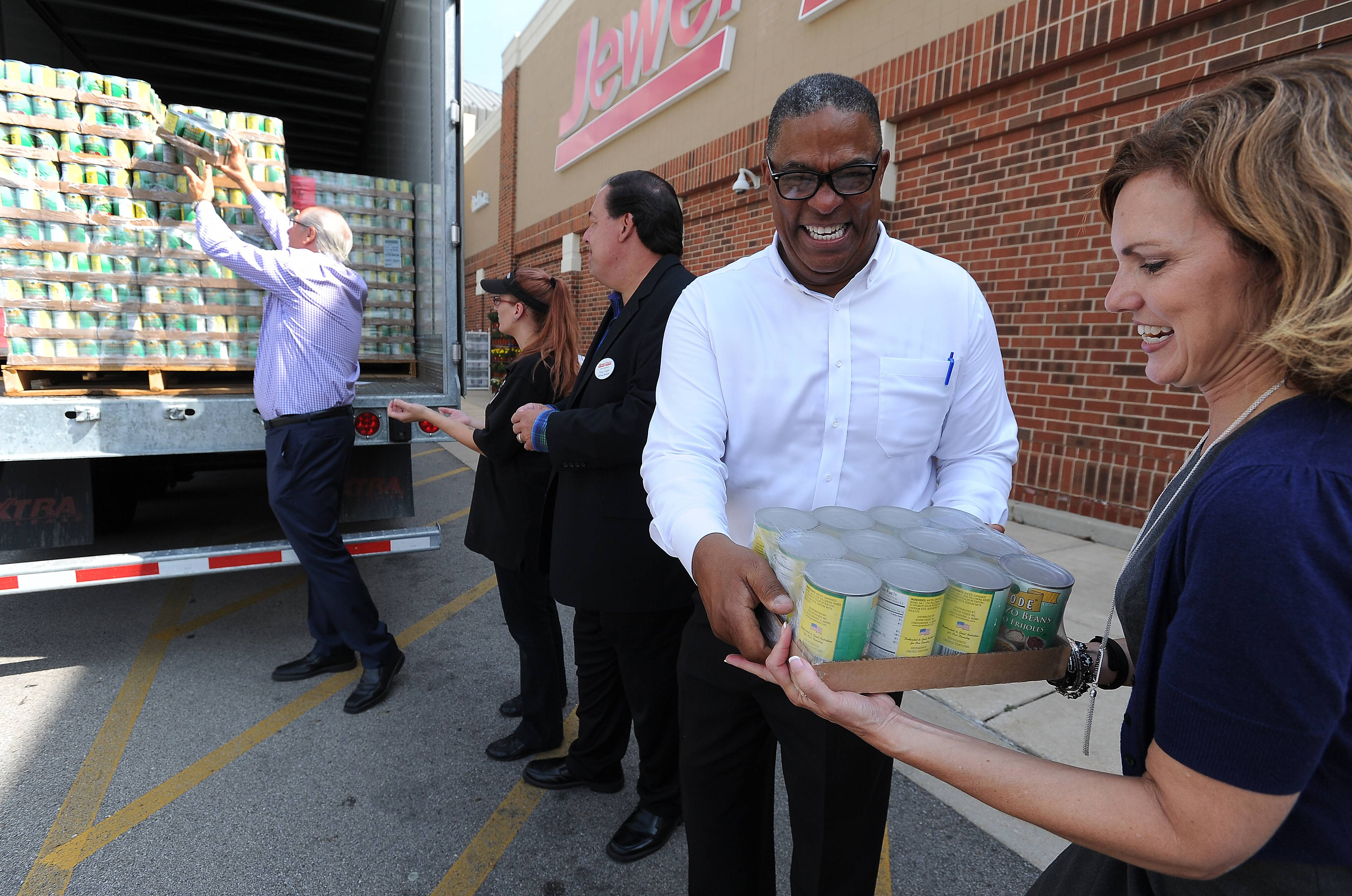 Goode Foods President Emile Johnson of Lincolnshire hands off beans to Julie Yurko, president and CEO of the Northern Illinois Food Bank, as they unload them at the Jewel-Osco in Bensenville. The food will be distributed to local food pantries.