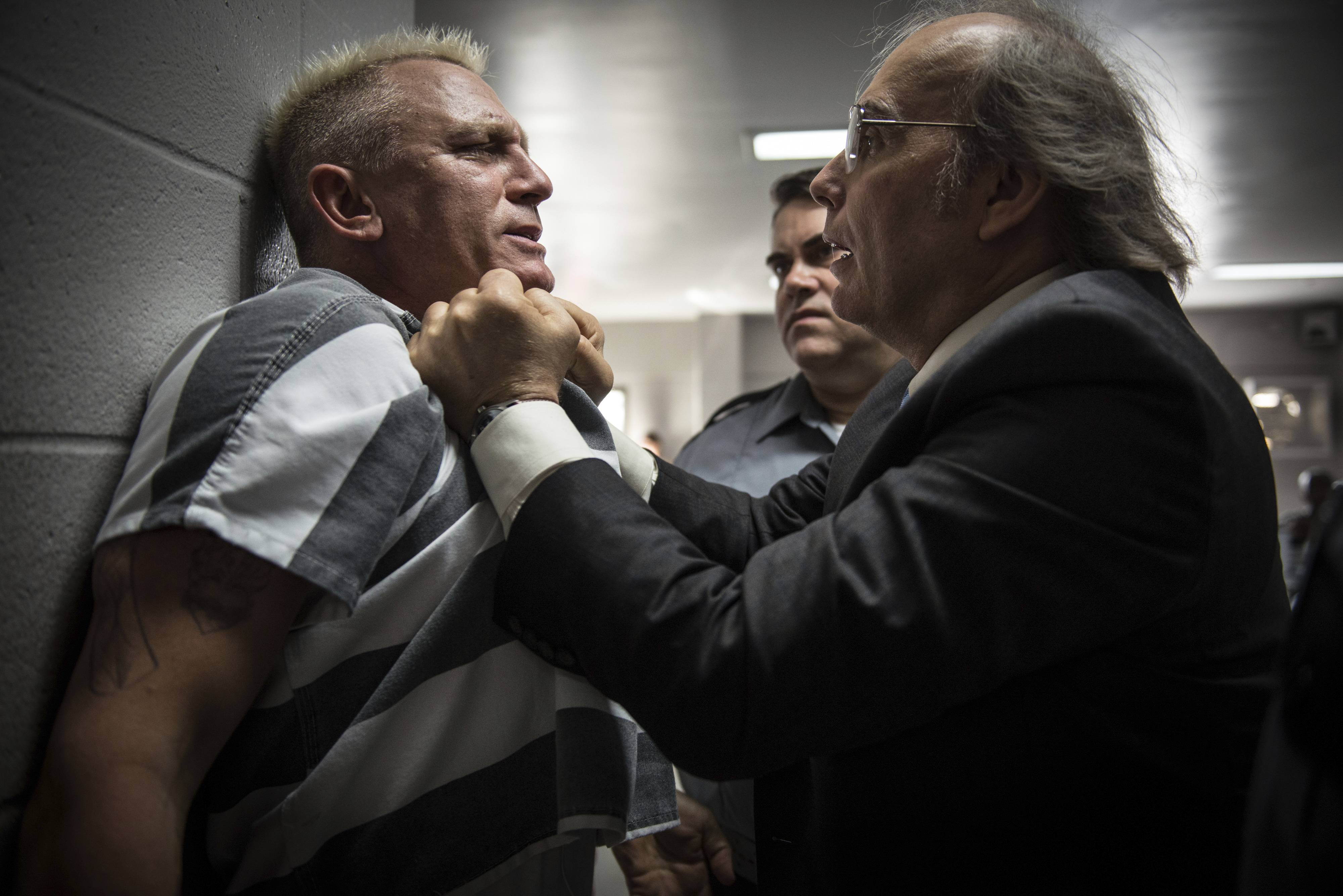 "Incarcerated bank vault robber Joe Bang (Daniel Craig) gets roughed up by a lying warden (Dwight Yoakam) in Steven Soderbergh's engaging comic caper tale ""Logan Lucky."""