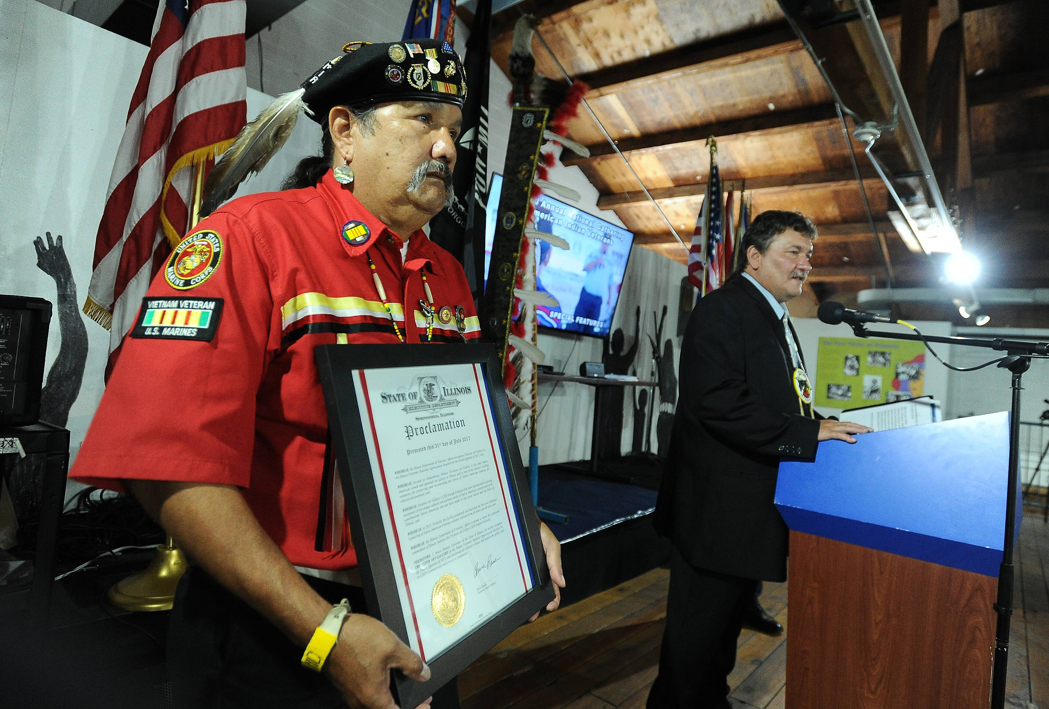 Native veteran Cmdr. Mike Pamonicutt, left, holds Gov. Rauner's proclamation honoring the Trickster Art Gallery in Schaumburg with the Illinois Veterans' Business Appreciation Award as Joseph Podlasek, CEO of the gallery, talks about the award to veterans and their families.