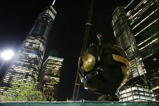 A section of the Koenig Sphere, a 25-ton bronze sphere damaged by the collapsing World Trade Center is lifted by crane into Liberty Park near One World Trade Center on Wednesday, Aug. 16, 2017, in New York. Plans were approved last year to move the sculpture from its temporary place in Battery Park at Manhattan's southern tip. The sphere once stood between the trade center's two towers. (AP Photo Peter Morgan)