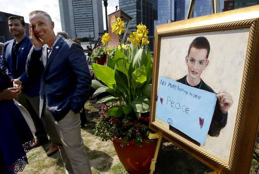 Bill Richard, second from left, father of fatal Boston Marathon bombing victim Martin Richard, brings his hand to his face while standing next to a painting of Martin, right, at the conclusion of groundbreaking ceremonies for a park named after his late son, Wednesday, Aug. 16, 2017, in Boston. Martin Richard, 8, was the youngest of three people killed when two bombs exploded near the Boston Marathon finish line on April 15, 2013. (AP Photo/Steven Senne)