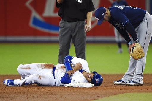 Toronto Blue Jays shortstop Ryan Goins (17) lies in pain after being tagged out and stepped on by Tampa Bay Rays shortstop Daniel Robertson (29) during the sixth inning of a baseball game, Wednesday, Aug. 16, 2017 in Toronto. (Nathan Denette/The Canadian Press via AP)
