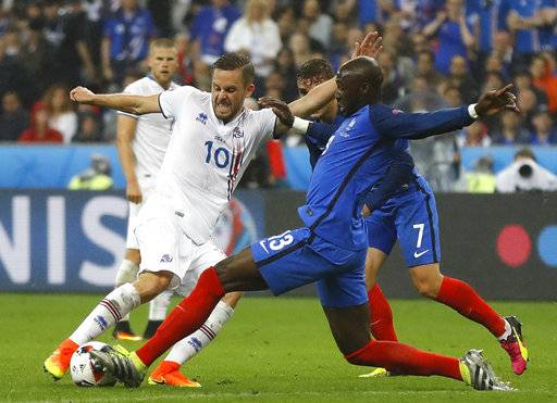 FILE - In this Sunday, July 3, 2016 file photo, Iceland's Gylfi Sigurdsson, left, and France's Eliaquim Mangala challenge for the ball during the Euro 2016 quarterfinal soccer match between France and Iceland, at the Stade de France in Saint-Denis, north of Paris, France. Everton says it has signed Iceland midfielder Gylfi Sigurdsson from Swansea for a club-record fee, further strengthening the team's attacking options to compensate for the departure of striker Romelu Lukaku. (AP Photo/Frank Augstein, File)