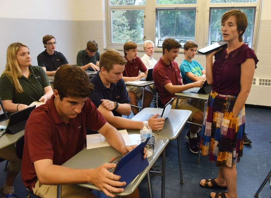 St. Viator High School junior Michael Ruben, left, and senior Andrew Kicinski work on their iPads in teacher Brigette Brankin's honors precalculus class during the first day classes Thursday the Arlington Heights school.