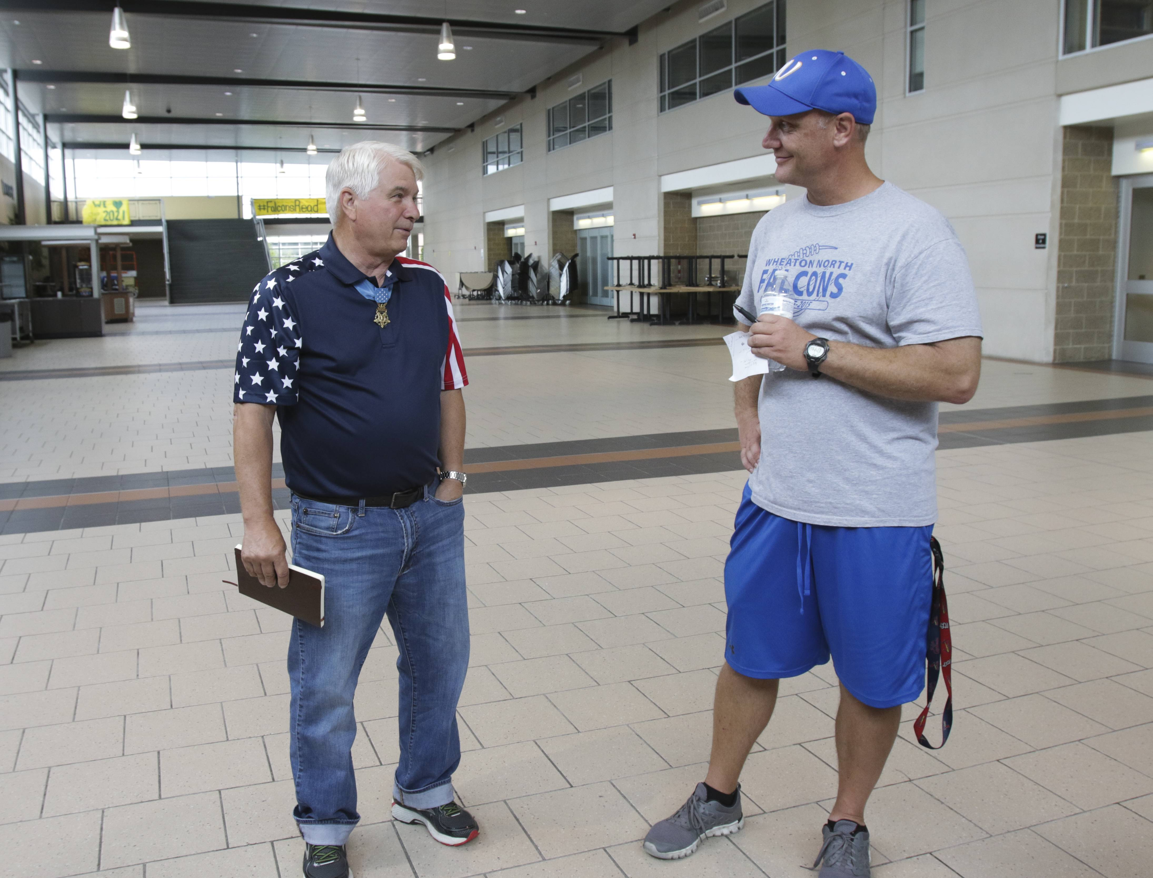 Jim McCloughan, a Medal of Honor recipient, speaks to Wheaton North High School football coach Joe Wardynski on Thursday before giving a talk to the football players.