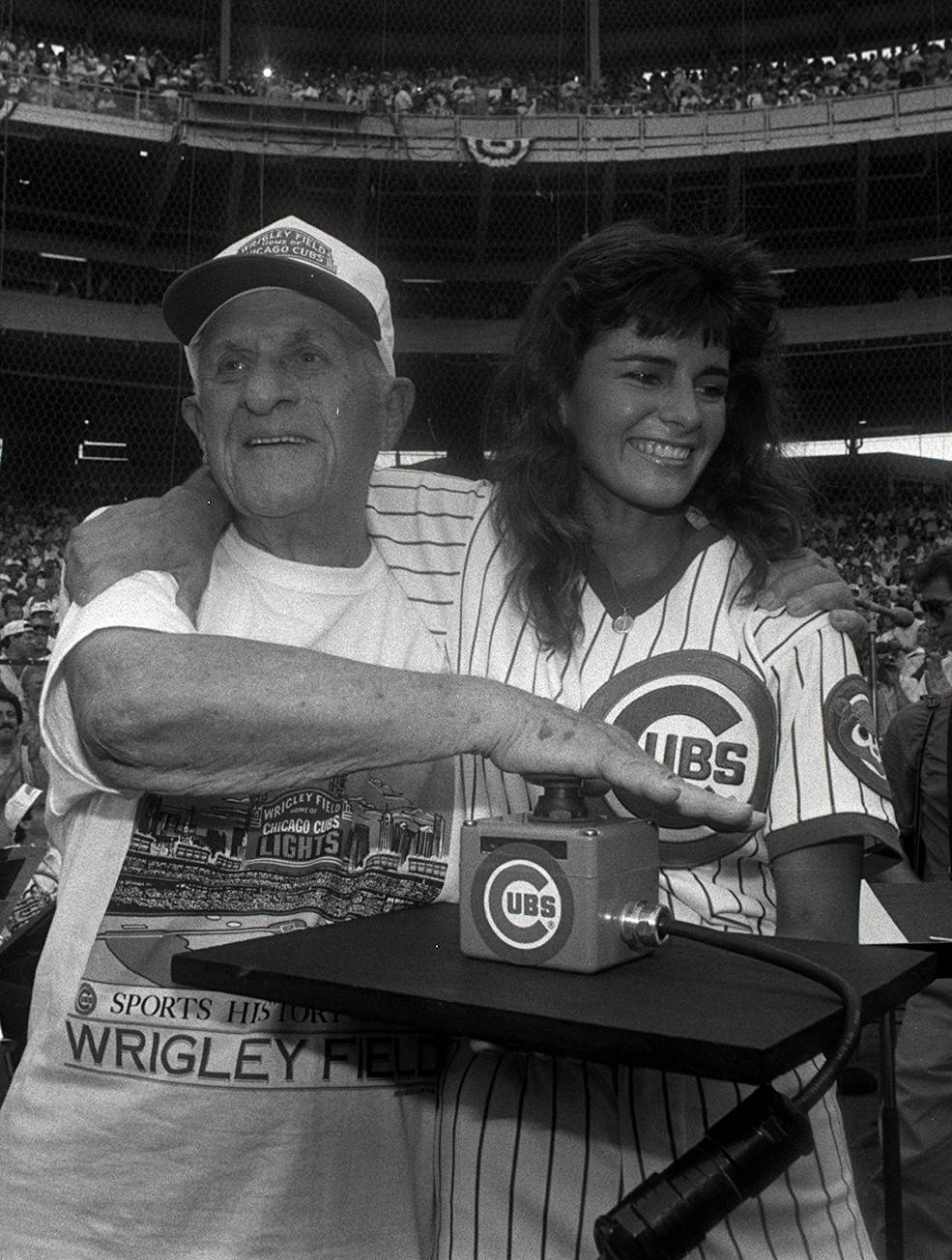 As the oldest season-ticket holder, 91-year-old Cubs fan Harry Grossman, punches the button switching on the lights for the first night game at Wrigley Field in Chicago on Aug. 8, 1988. That game was postponed by rain, but the Cubs have a surprisingly good record in night games at Wrigley since then.