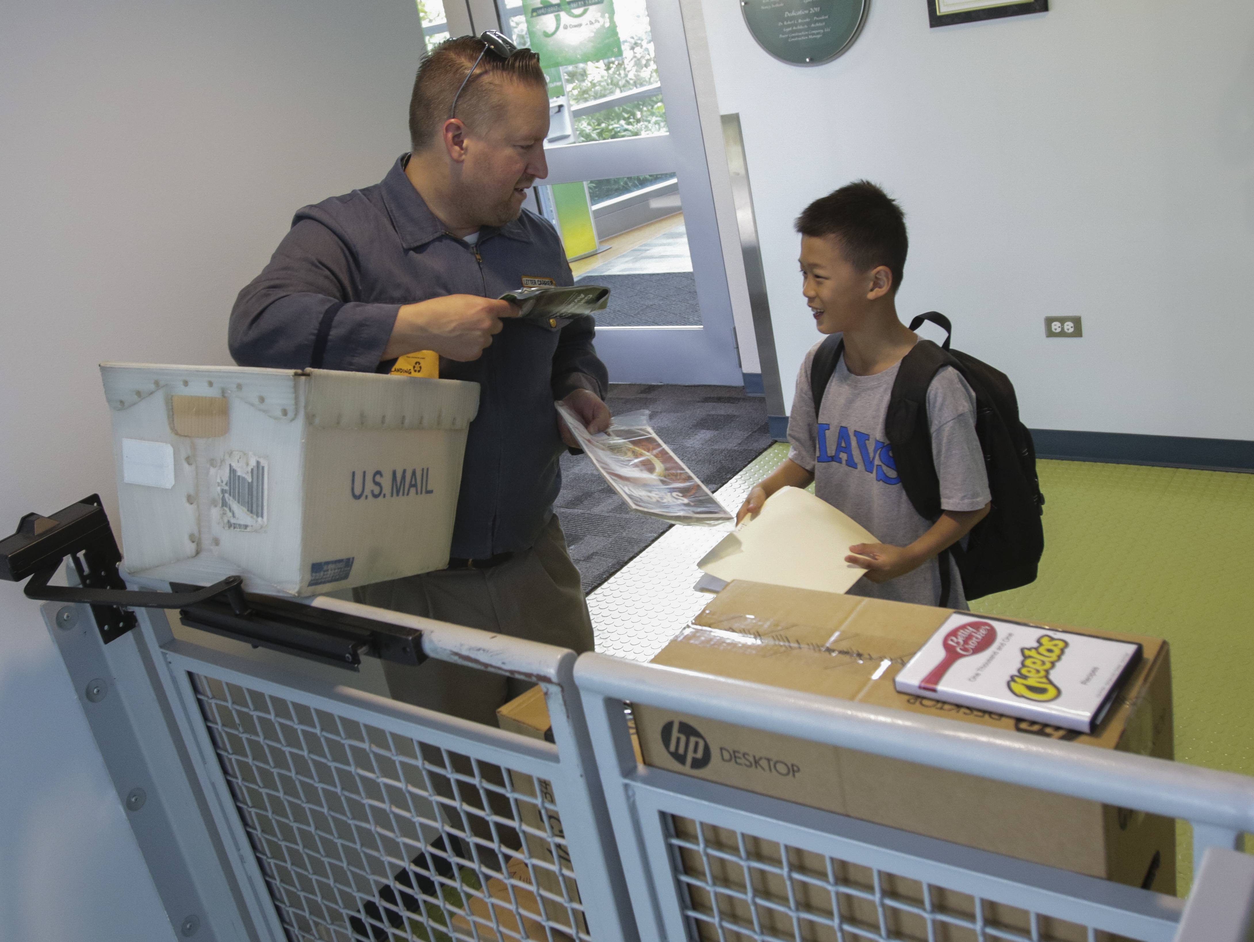 Justin Wagner, lead instructor, plays the part of a postal worker, with student Ryan Chen, 10, of Naperville, at GenCyber camp at the College of DuPage in Glen Ellyn. Students use skills to solve cyber crimes at the college's Homeland Security Training Center.