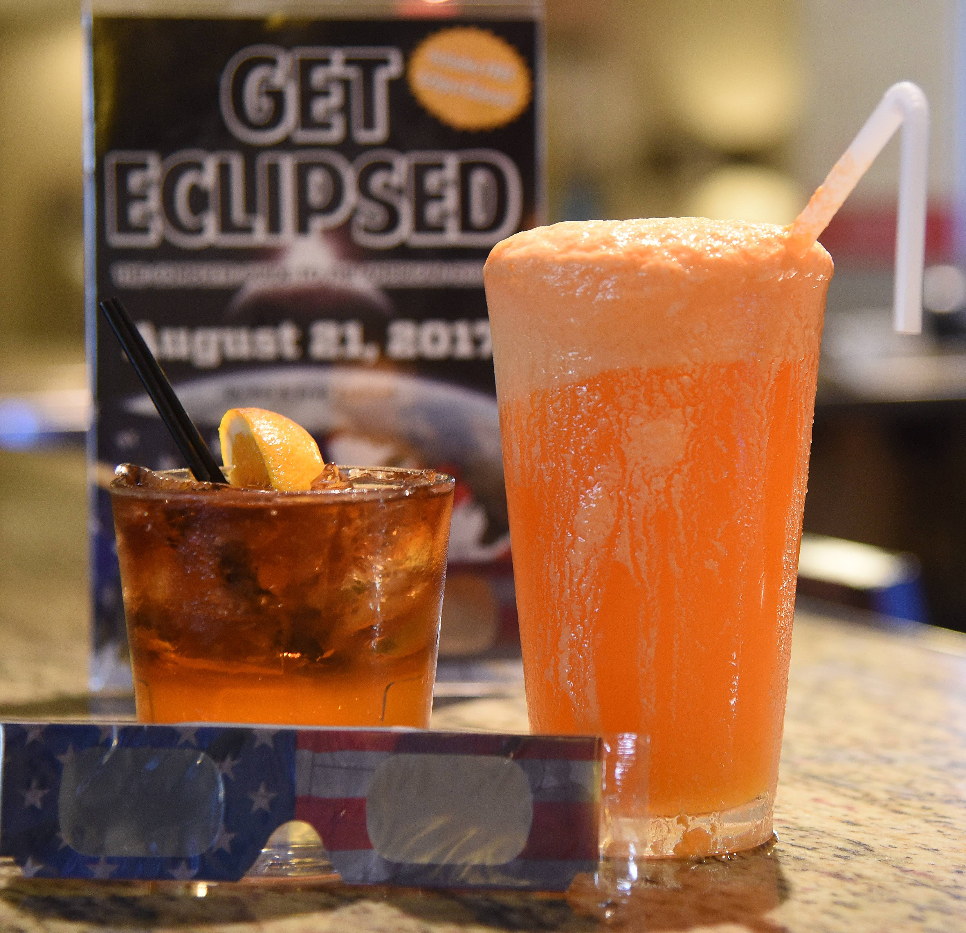 Pheasant Run Resort in St. Charles has created a pair of drinks inspired by the eclipse. Adults can sip a cocktail made with dark rum, left, while kids can celebrate with a creation featuring orange soda and ice cream.
