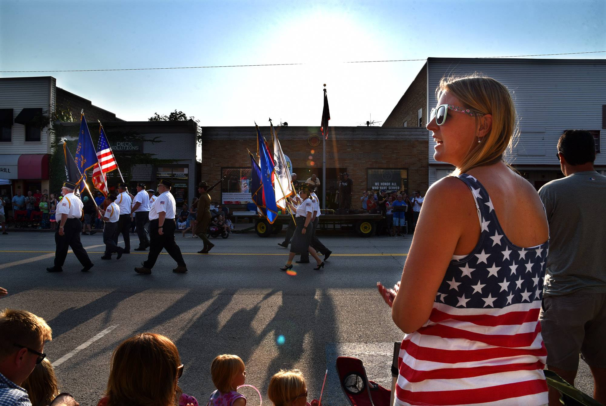 Angela Spore of Elburn wears a patriotic shirt as a color guard marches past to open the Elburn Days Parade in downtown Elburn Friday evening.