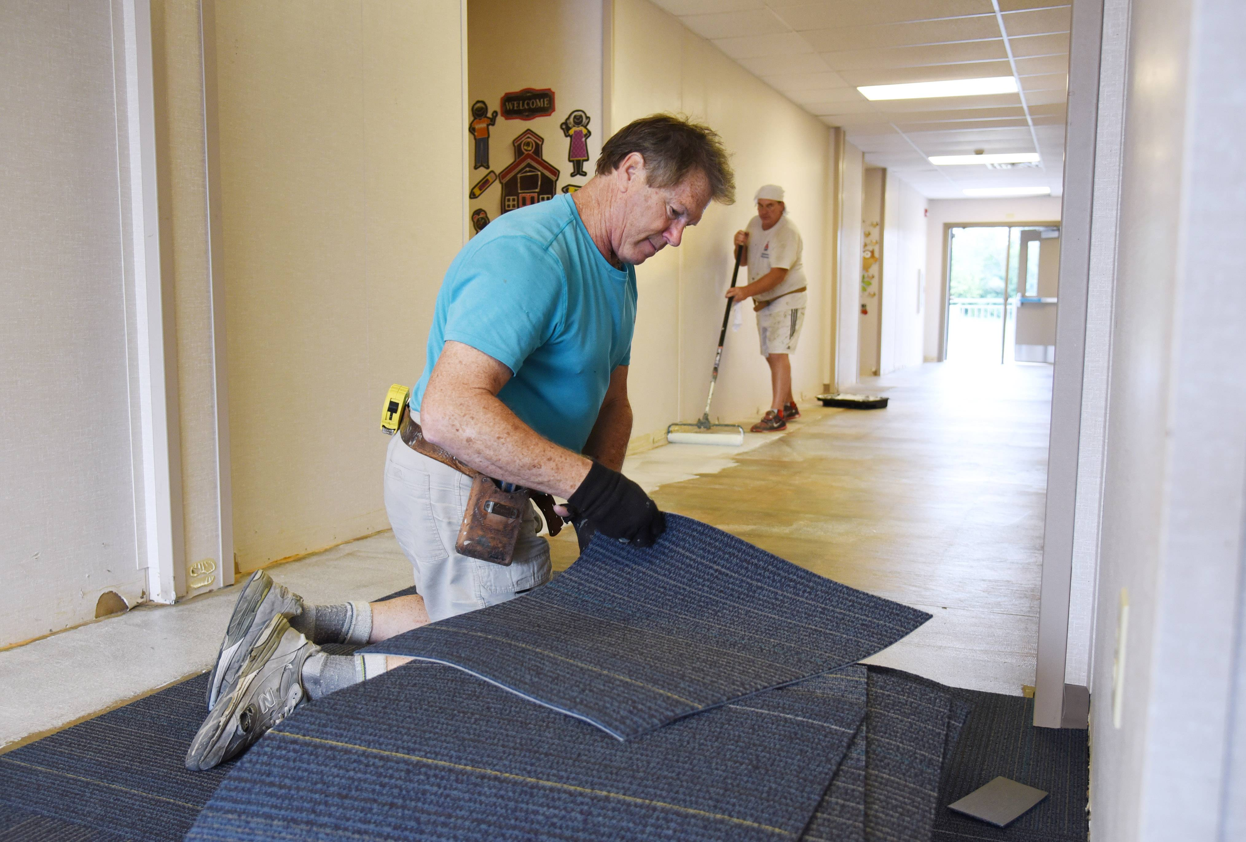 Mike Beier, left, and Mike Ulane of Prospect Heights' M & M Carpet, glue carpet squares in the hallway of the temporary mobile classroom building behind Murphy Elementary School in Round Lake on Friday. The school is set to open Monday's after it was damaged by flooding last month.