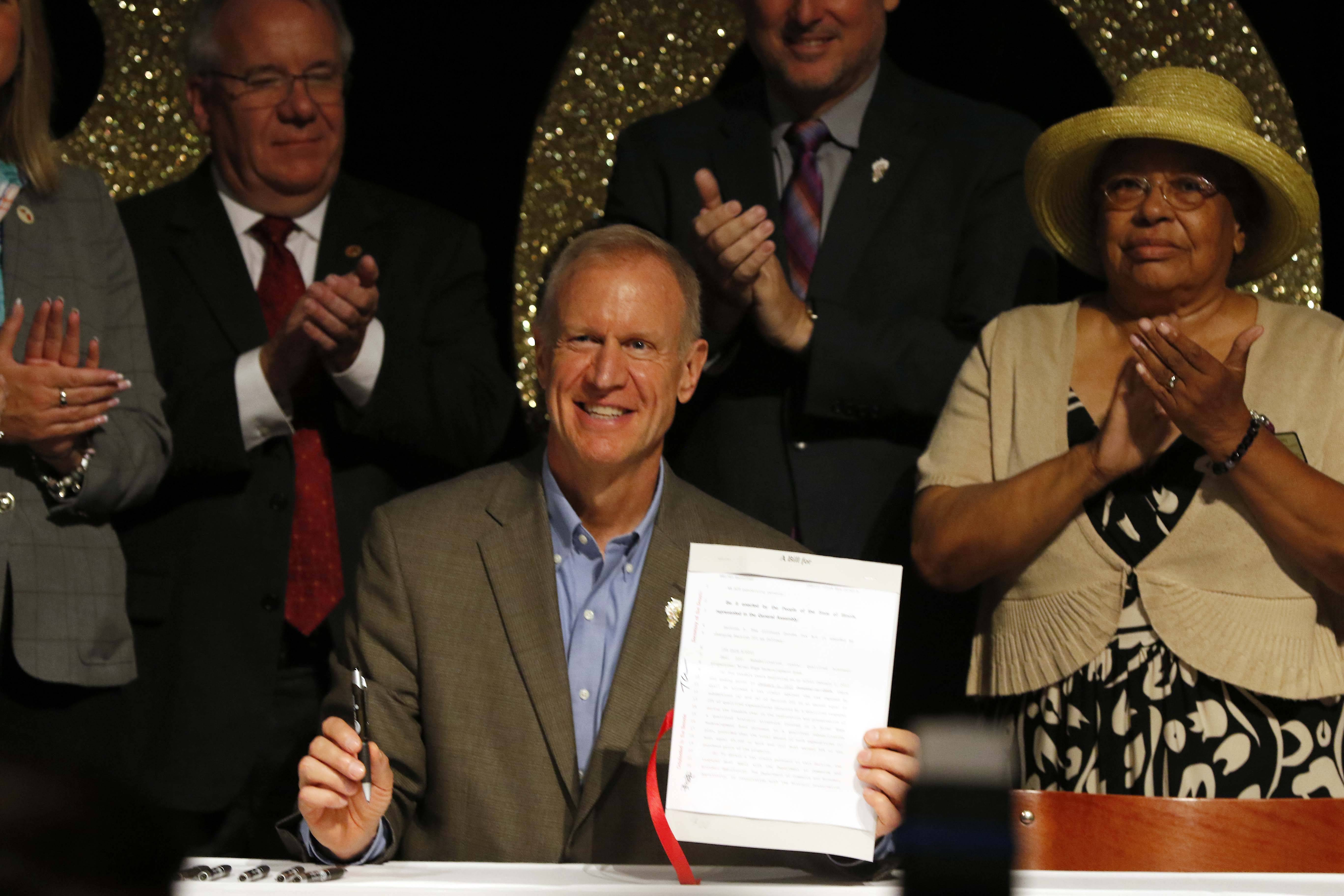 Gov. Bruce Rauner signs a bill Friday in Aurora that extends the River Edge Redevelopment Zone Historic Tax Credit to help cities including Aurora and Elgin revitalize old properties.