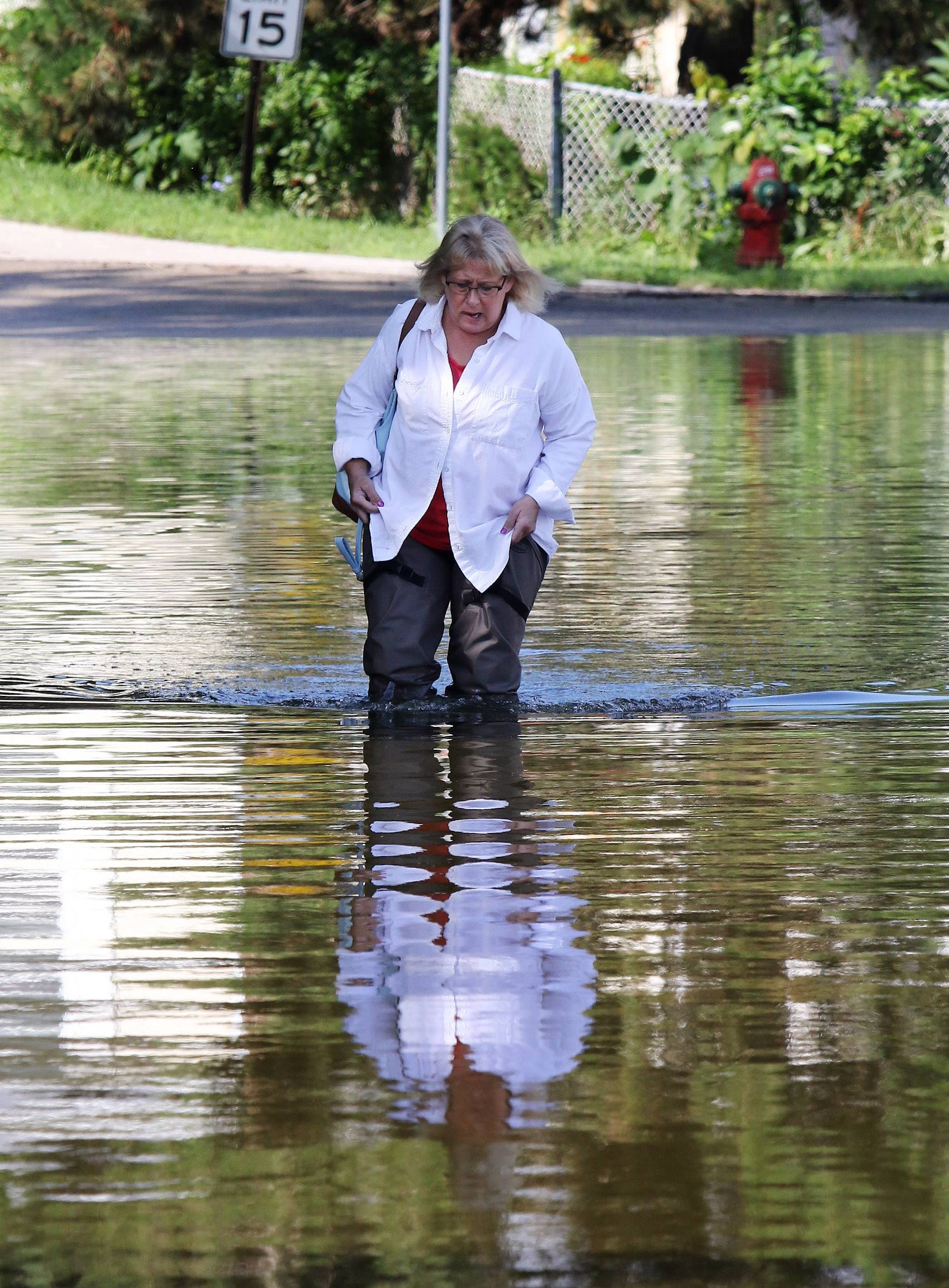 Karen Burt walks along Kings Road from her home during flooding in Fox Lake in July. Gov. Bruce Rauner toured Fox Lake on Friday to get a firsthand assessment of damage caused by the flooding.