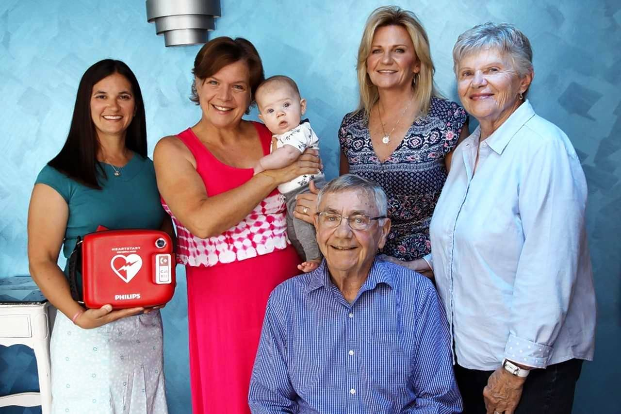 Robert McCue, seated, had his life saved June 9 when he went into cardiac arrest while attending his granddaughter's play at Center Stage Theater in Naperville. Melissa Lund, left, used a defibrillator bought by theater owner Kandiss Hernandez, holding her grandson, to help revive him before paramedics arrived. Also pictured are McCue's daughter Mary McCue, a nurse who also helped resuscitate Robert, and his wife, Judy McCue, right.