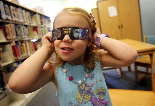 Emmalyn Johnson, 3, tries on her free pair of eclipse glasses at Mauney Memorial Library in Kings Mountain, N.C.