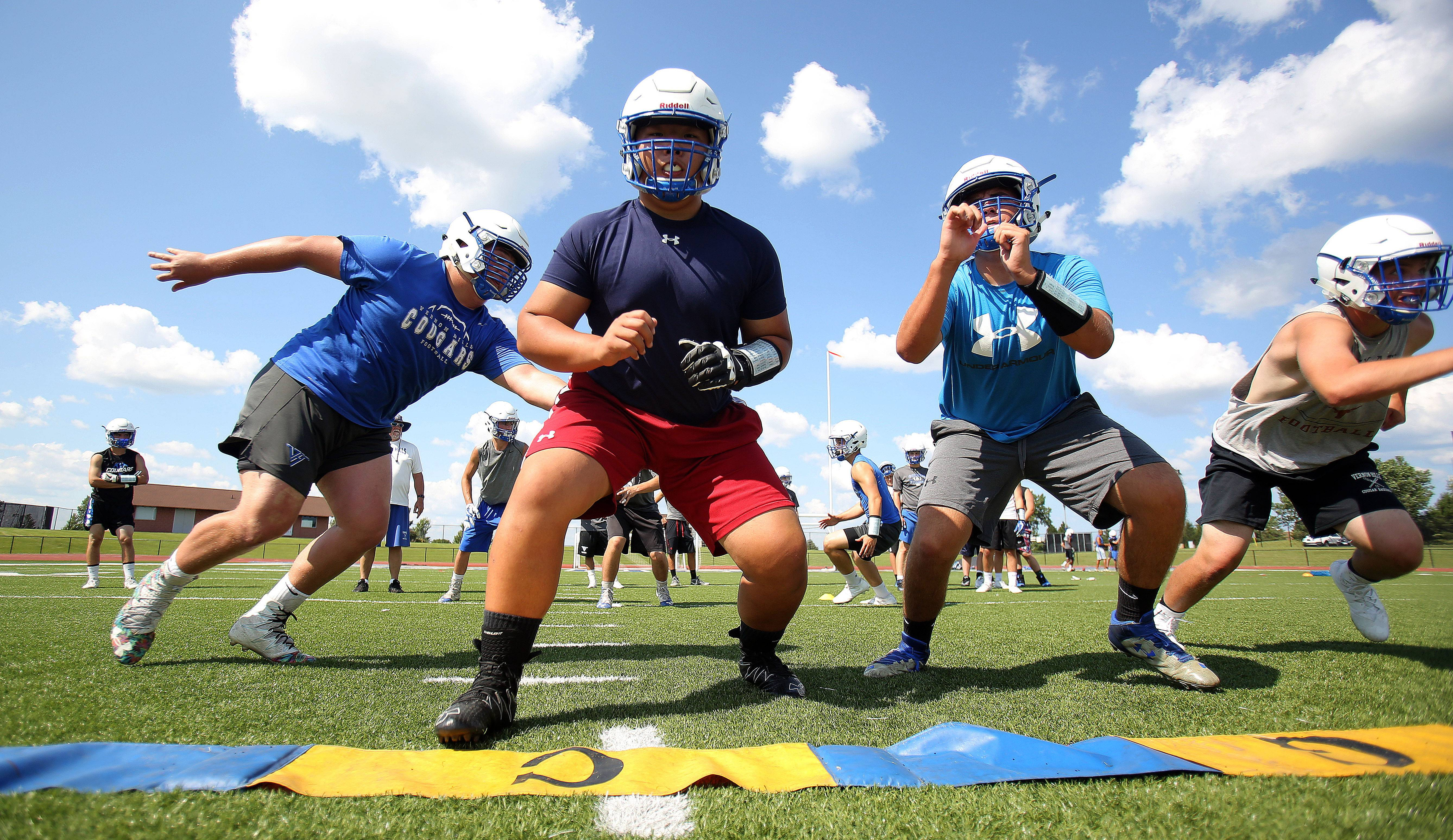 Lineman run through plays during an early football practice at Vernon Hills.