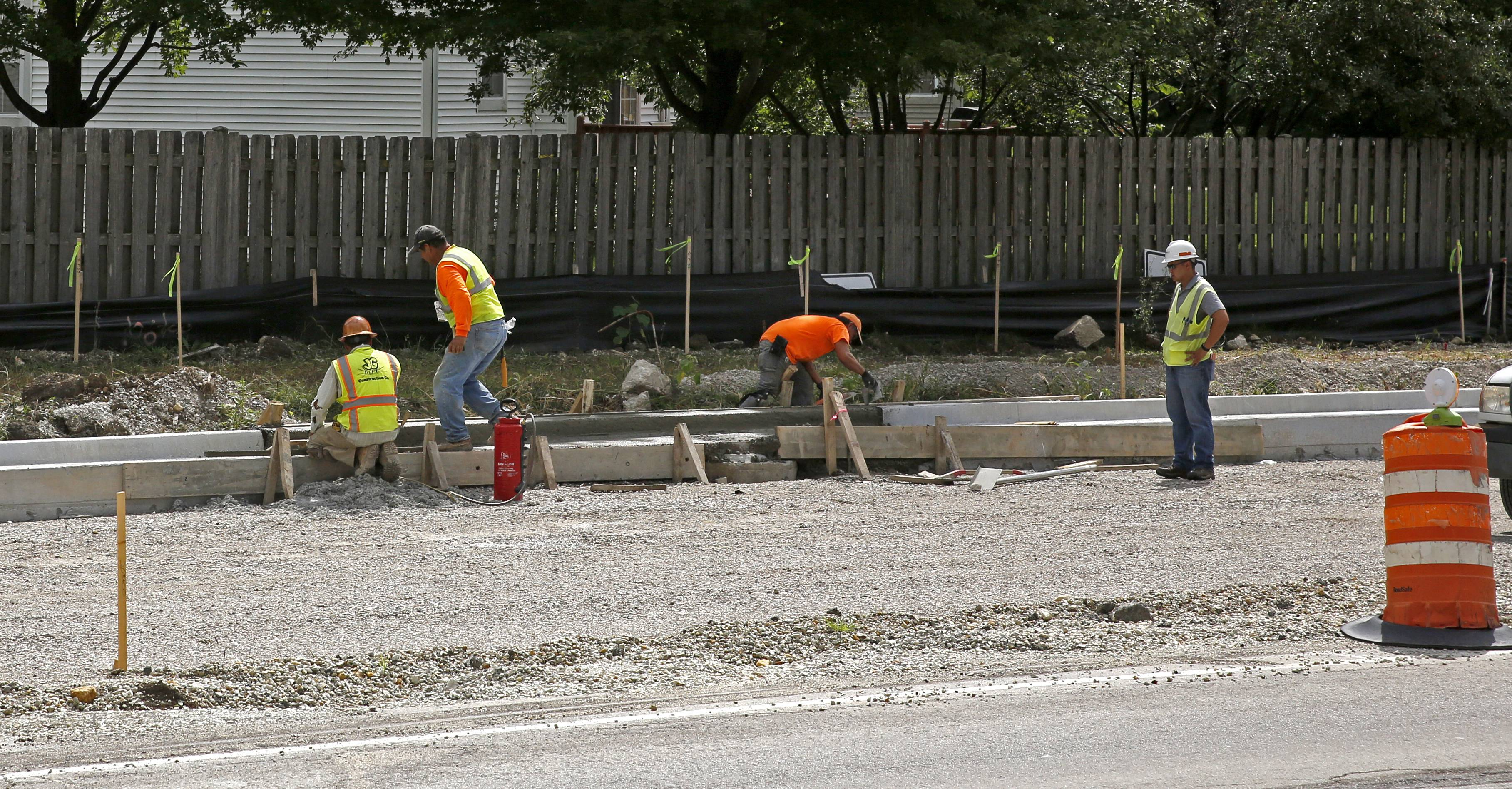 Construction crews build curbs Thursday as part of a $6.5 million project to add turn lanes at 95th Street and Plainfield/Naperville Road. The work has neighbors raising concerns about noise, dust and fumes.