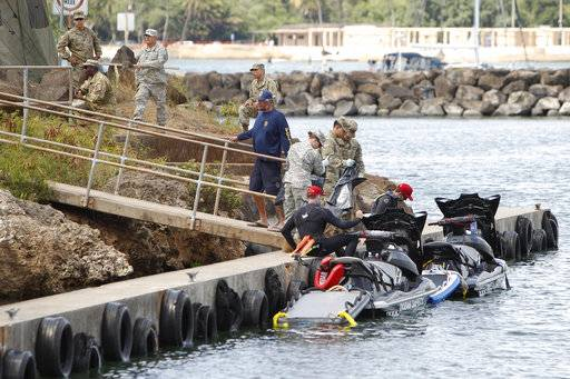 Honolulu ocean safety lifeguards on jet skis hand over materials to military personnel stationed at a command center at a boat harbor, Wednesday, Aug. 16, 2017, in Haleiwa, Hawaii. An Army helicopter with five on board crashed several miles off Oahu's North Shore late Tuesday. (AP Photo/Marco Garcia)