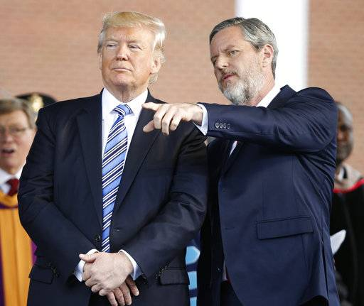 "In this photo taken May 13, 2017, President Donald Trump stands with Liberty University President Jerry Falwell Jr. in Lynchburg, Va. Falwell, and an early backer of Trump, said the president had made a ""bold truthful statement� about the demonstration. Falwell said the president's remarks were a clear repudiation of white supremacists, Nazis and the Ku Klux Klan. (AP Photo/Steve Helber)"