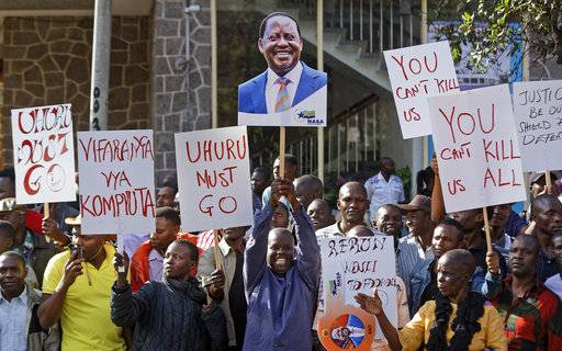 A supporter of main opposition leader Raila Odinga holds a placard of his face, center, as they make a small demonstration outside the Supreme Court in Nairobi, Kenya, Friday, Aug. 18, 2017. Dozens of supporters gathered in front of the court building where opposition lawyers were expected to file a petition contesting President Uhuru Kenyatta's re-election. (AP Photo/Ben Curtis)