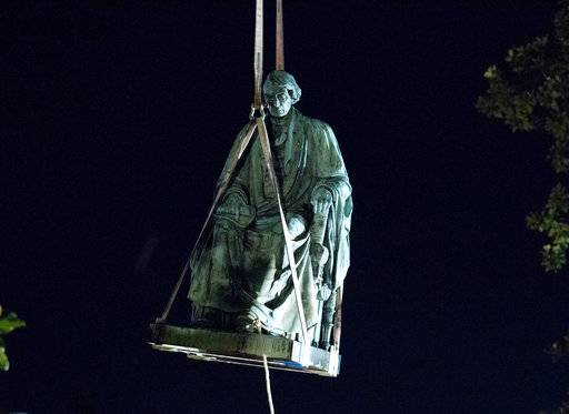 Workers use a crane to lift the monument dedicated to U.S. Supreme Court Chief Justice Roger Brooke Taney after it was was removed from outside Maryland State House, in Annapolis, Md., early Friday, Aug. 18, 2017. Maryland workers hauled several monuments away, days after a white nationalist rally in Charlottesville, Virginia, turned deadly. ( AP Photo/Jose Luis Magana)