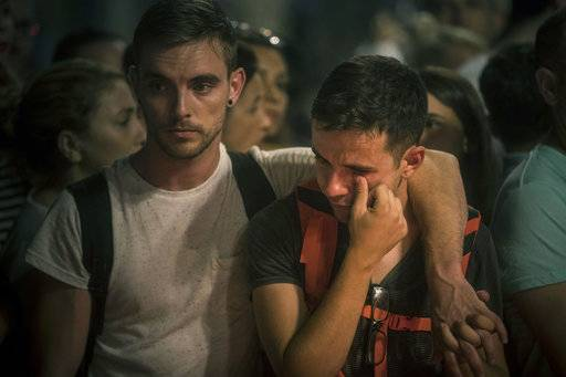 A man cries in front of a memorial tribute to the victims of the terrorist attack in Barcelona, Spain, Saturday Aug. 19, 2017. Police on Friday shot and killed five people carrying bomb belts who were connected to the Barcelona van attack, as the manhunt intensified for the perpetrators of Europe's latest rampage claimed by the Islamic State group. (AP Photo/Santi Palacios)