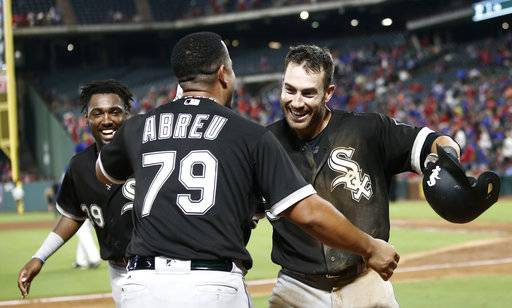 Chicago White Sox's Nicky Delmonico (30) is congratulated by Jose Abreu (79) after hitting an inside-the-park home run as Alen Hanson (39) watches against the Texas Rangers in the eighth inning of a baseball game Friday, Aug. 18, 2017, in Arlington, Texas. (AP Photo/Mike Stone)