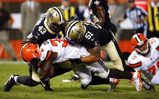 FILE - In this Aug. 10, 2017, file photo, Cleveland Browns running back Isaiah Crowell (34) is tackled by New Orleans Saints linebacker Manti Te'o (51) and Marcus Williams (43) during the first half of an NFL preseason football game in Cleveland. Te'o signed with the Saints during the offseason after four years with the San Diego Chargers. (AP Photo/Ron Schwane, File)