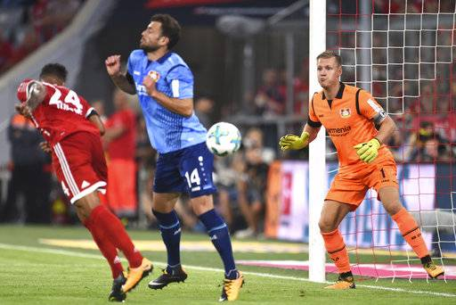 Bayern Munich's Corentin Tolisso, left, scores past Bayer Leverkusen's goalkeeper Bernd Leno during the German Bundesliga soccer match in the Allianz Arena in Munich, Germany, Friday Aug. 18, 2017. (Andreas Gebert/dpa via AP)