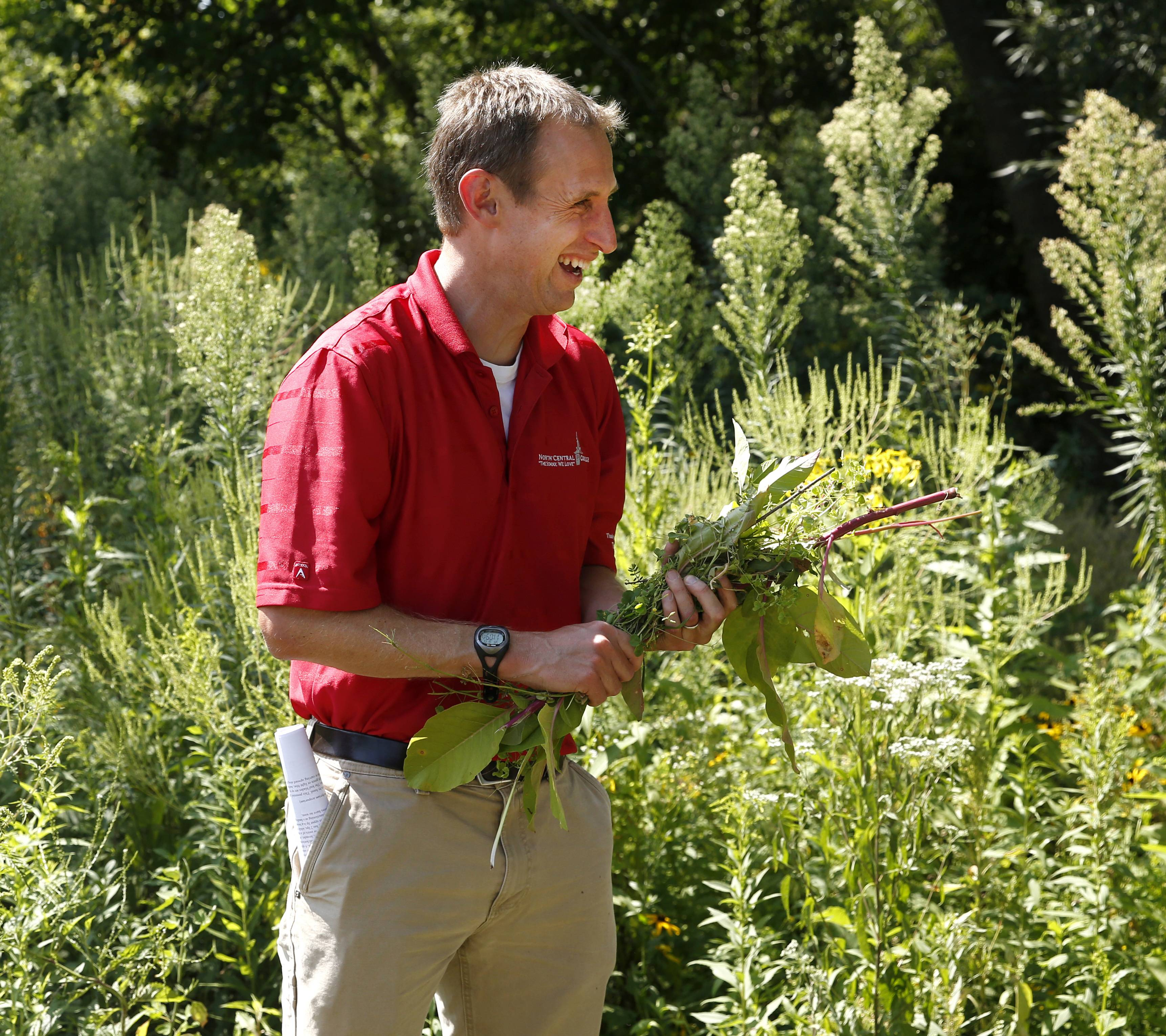 Greg Ruthig, associate professor of biology at North Central College, is encouraged to be planting more native prairie plants between the school's stadium and the DuPage River. Above, Ruthig is holding an invasive plant, pokeweed, that he pulled out Saturday.