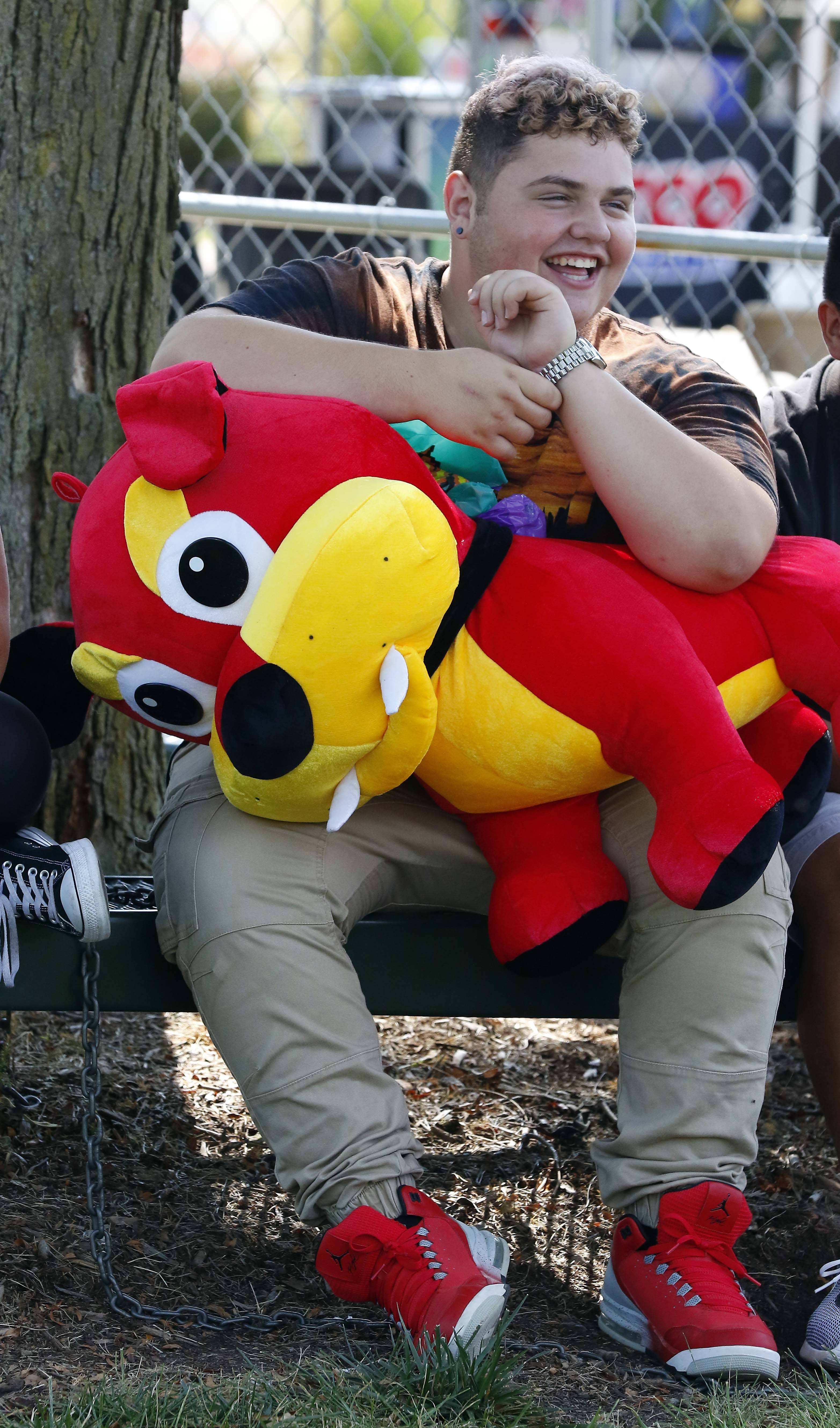 """I won it for my girl, so that when I'm not around she has a guard dog,"" said Dylan Hartigan, 15, of South Elgin about the giant red bulldog on his lap. Hartigan won the prize on his first try Saturday during South Elgin's Riverfest Express."