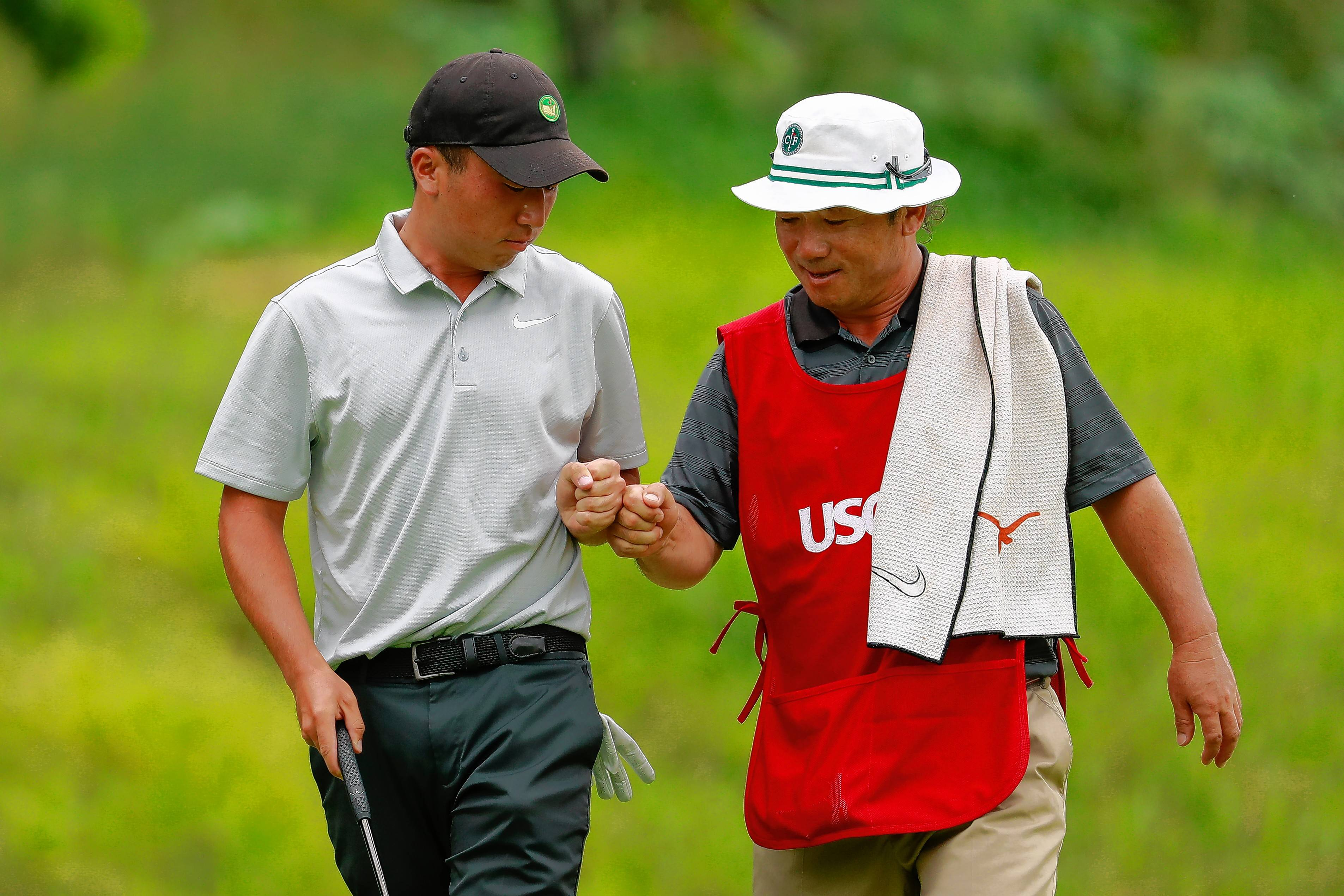Doug Ghim fist bumps his father on the fifth hole during the semifinal round of match play of the 2017 U.S. Amateur at The Riviera Country Club in Los Angeles, Calif. on Saturday, Aug. 19, 2017.