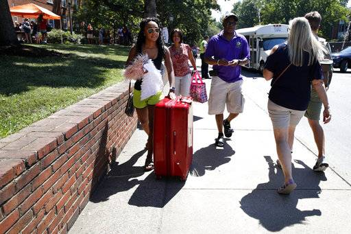 Malia Valentine, 18, of Yorktown, Va., left, moves her things into her new dormitory with her mother Michelle Valentine and father Carl Valentine, during move-in for first year students at the University of Virginia, Friday, Aug. 18, 2017, in Charlottesville, Va., a week after a white nationalist rally took place on campus.