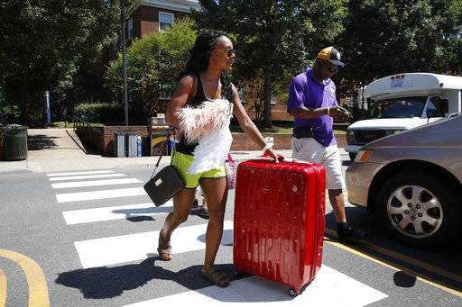 Malia Valentine, 18, of Yorktown, Va., left, and her father Carl Valentine, gather her items during move-in for first year students at the University of Virginia, Friday, Aug. 18, 2017, in Charlottesville, Va., a week after a white nationalist rally took place on campus.