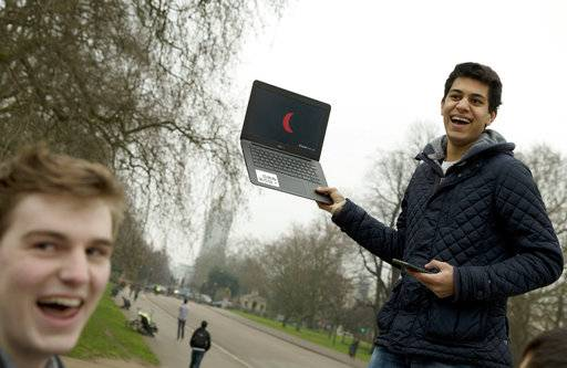 FILE - In this Friday, March, 20, 2015 file photo, a student holds up a laptop computer with a live television feed showing the progress of total solar eclipse to a group of his friends, near the Albert Memorial in London. For the 2017 eclipse in the United States, NASA and other news and television outlets will offer live coverage of the celestial event.