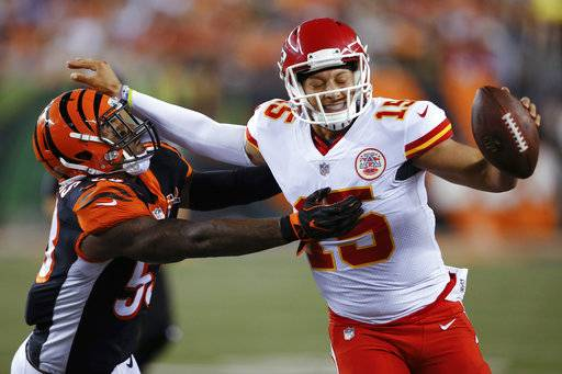 Kansas City Chiefs quarterback Patrick Mahomes (15) stiff-arms Cincinnati Bengals outside linebacker Marquis Flowers (53) during the second half of an NFL preseason football game, Saturday, Aug. 19, 2017, in Cincinnati.