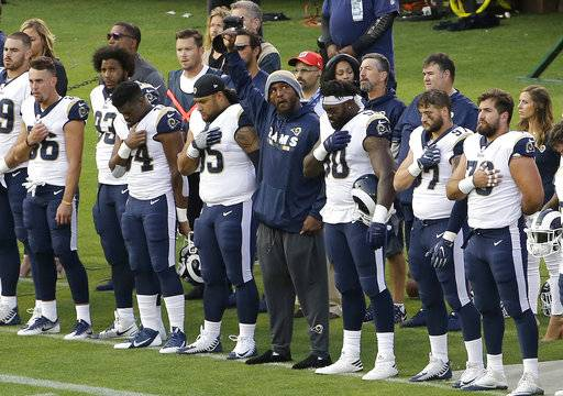 Los Angeles Rams linebacker Robert Quinn, center, raises his fist during the national anthem before an NFL preseason football game against the Oakland Raiders in Oakland, Calif., Saturday, Aug. 19, 2017.