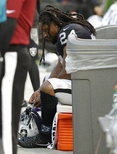 Oakland Raiders running back Marshawn Lynch sits on the bench during the national anthem before an NFL preseason football game  against the Los Angeles Rams in Oakland, Calif., Saturday, Aug. 19, 2017.